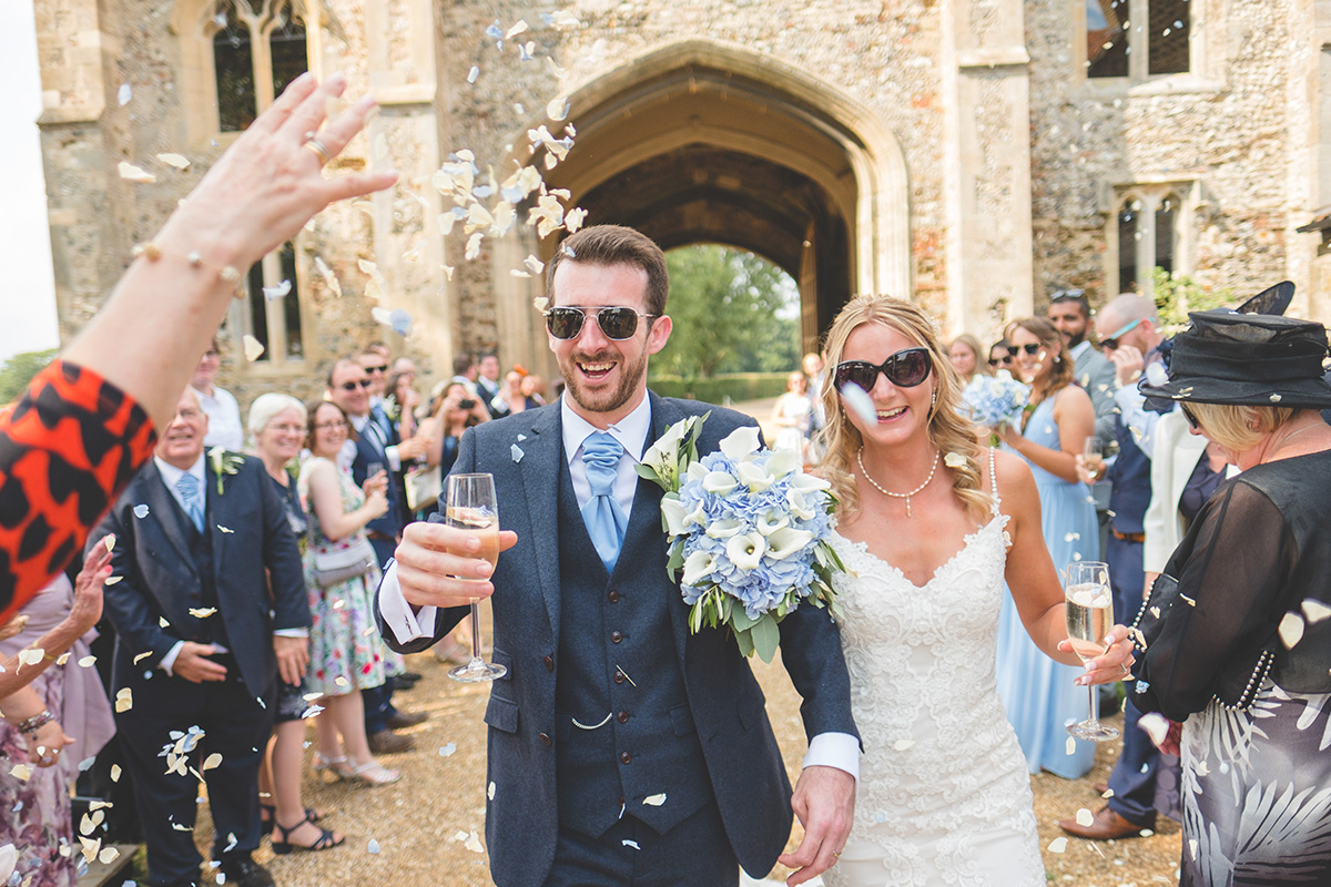 The happy newlyweds look cool in their sunglasses on their summer wedding day at Pentney Abbey in Norfolk