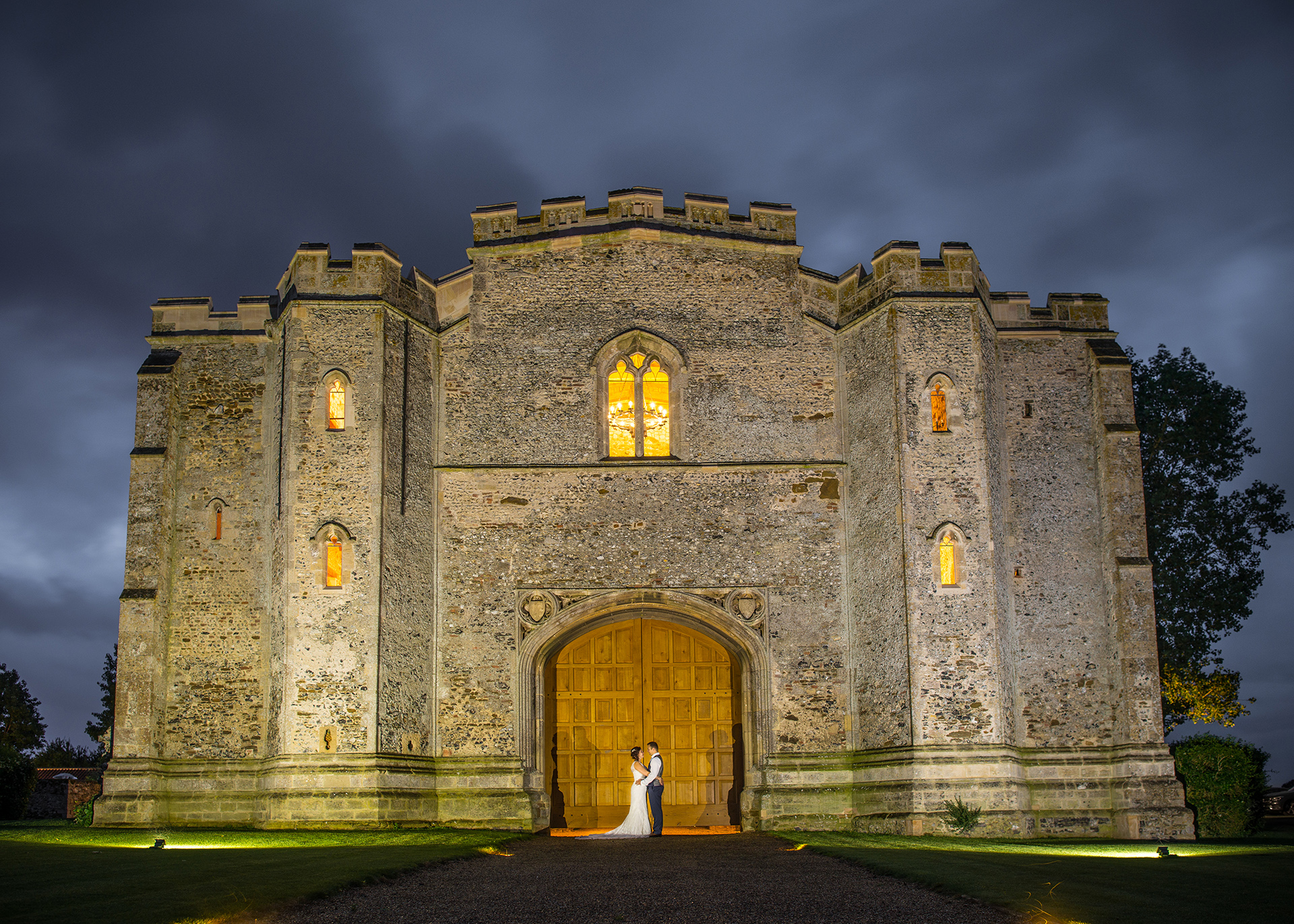 The bride and groom pose for a wedding photo in the evening at Pentney Abbey