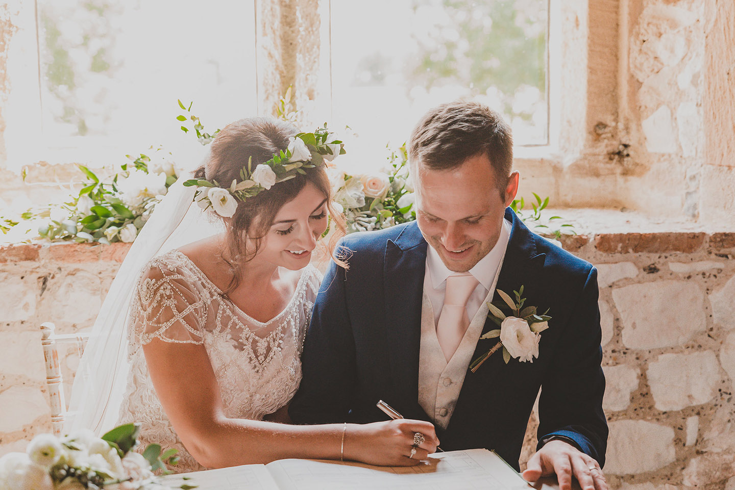 The happy couple sign the register following their wedding ceremony in Norfolk