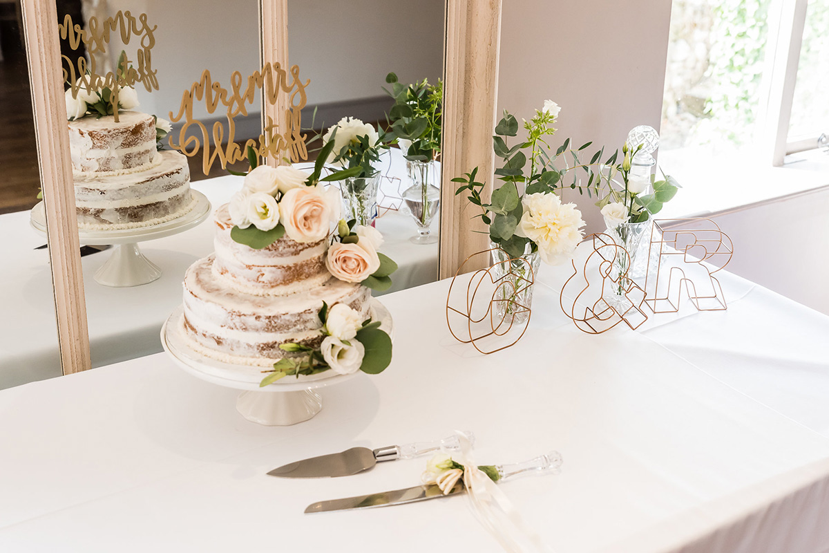 A beautiful three-tier semi-naked wedding cake decorated with pretty pale roses and a rose gold cake topper at Pentney Abbey