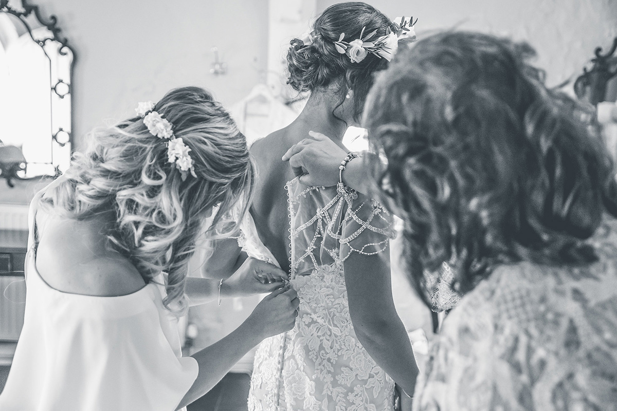 The bridesmaids make the last touches to the bride's look as they prepare for the day ahead at Pentney Abbey